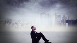 雨の中座る男性